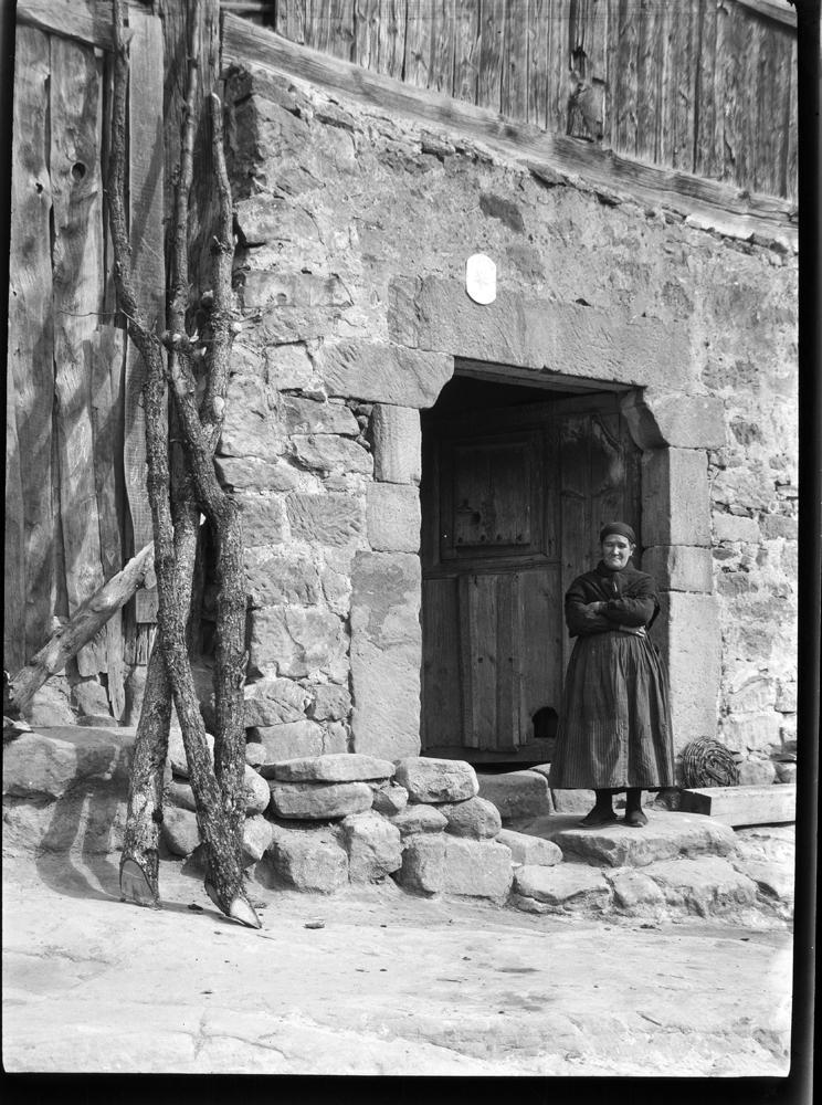 Duruelo. Hausportal [Puerta de la casa y mujer de negro con pañ